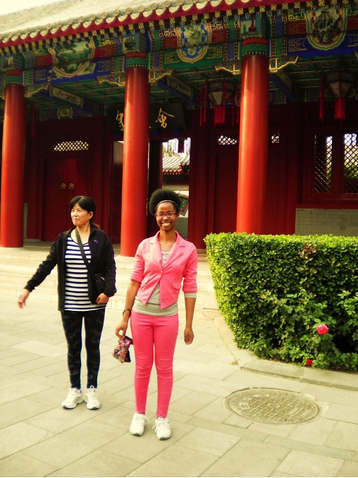 woman wearing pink standing next to other woman in front of red Chinese building with pillars in front