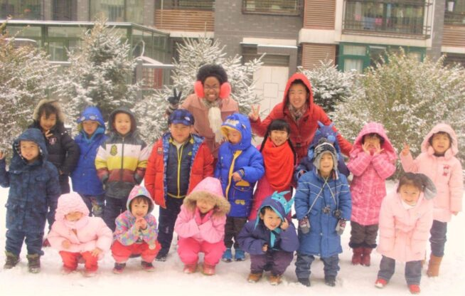 teacher smiling with a bunch of students in the snow